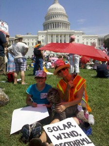 mom and daughter sitting on the grass at Stop the Frack Attack rally