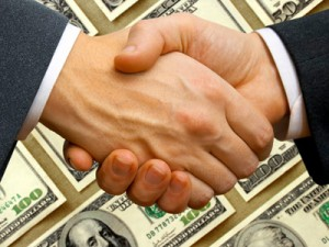 Shaking hands in front of pile of money