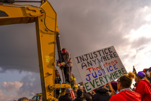 Happy American Horse attaching himself to an excavator at the construction site of the Dakota Access Pipeline on 31 August 2016. Photo by Rob Wilson for Bold Alliance