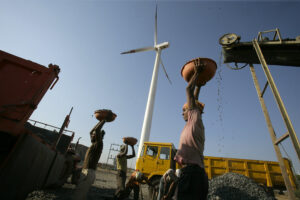 A laborer is seen working at a deisel powered crusher infont of a wind turbine.